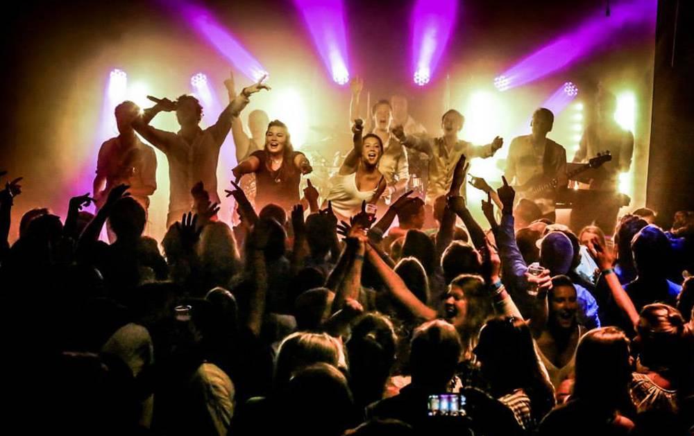 Feestband Hermes House Band op het podium met publiek